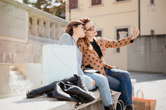 Female shoppers taking selfie in front of fountain, Arezzo, Toscana, Italy