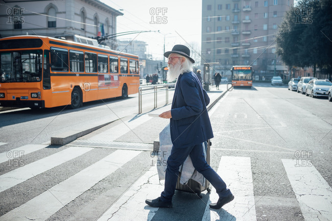 Senior businessman with wheeled luggage walking on pedestrian crossing, Milano, Lombardia, Italy
