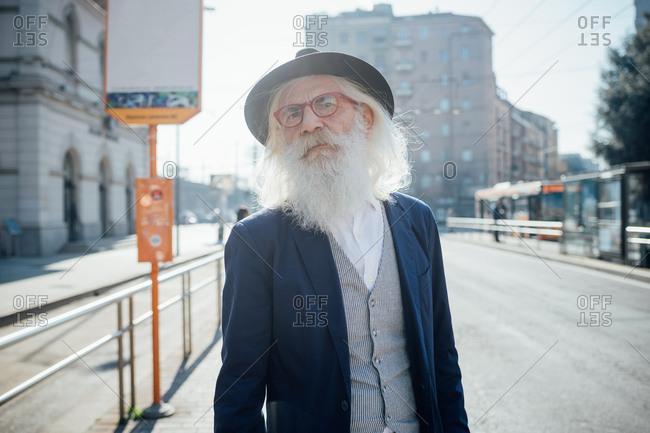 Senior businessman waiting at bus stop, Milano, Lombardia, Italy