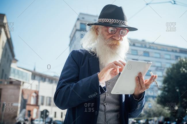 Senior businessman using digital tablet in city, Milano, Lombardia, Italy