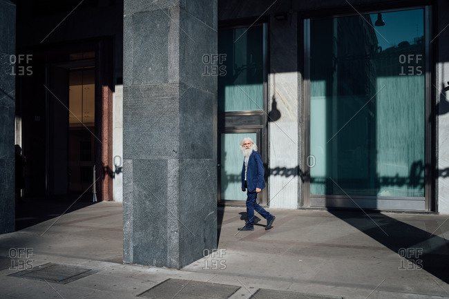 Senior businessman passing office building, Milano, Lombardia, Italy