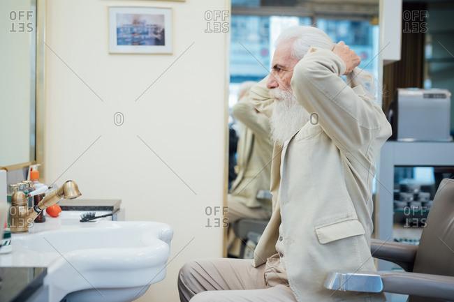 Senior businessman tying hair in salon