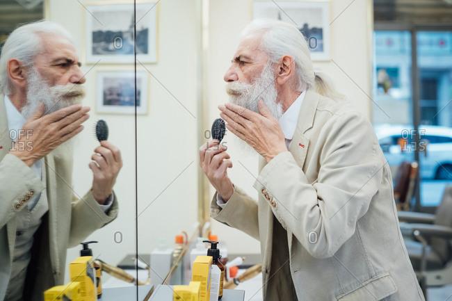 Senior businessman brushing beard in salon