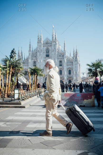 Senior businessman with wheeled luggage passing Milan Cathedral in background, Milano, Lombardia, Italy