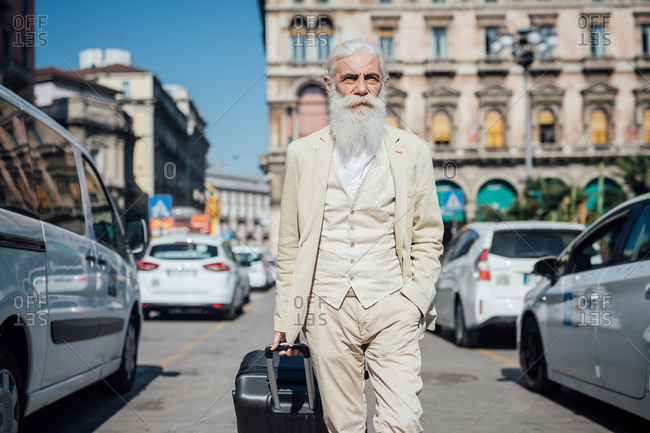 Senior businessman with wheeled luggage in city, Milano, Lombardia, Italy