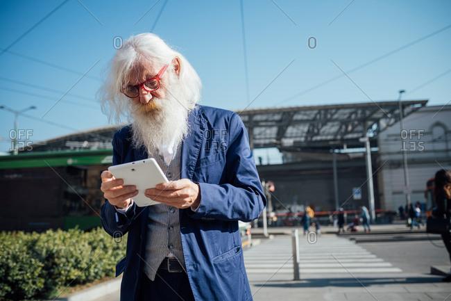 Senior businessman using digital tablet at bus terminal, Milano, Lombardia, Italy