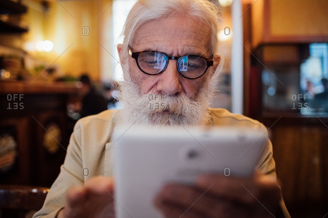 Senior businessman using digital tablet in cafe