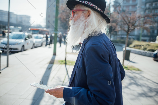 Senior businessman using digital tablet on pavement, Milano, Lombardia, Italy