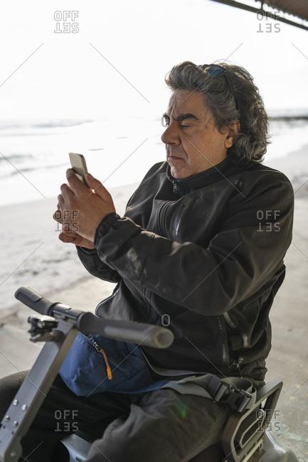Man on wheels using smartphone at seaside