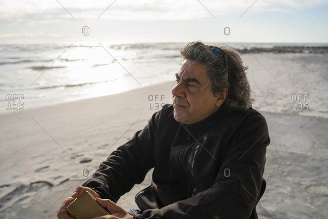 Man on wheels with smartphone enjoying seaside