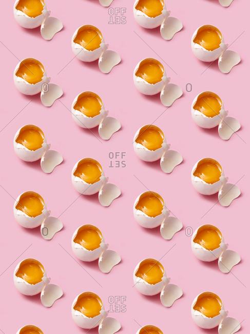Broken eggs arranged in rows on pink background
