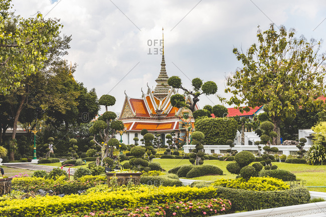 Buddhist temple, landscaped garden in foreground, Bangkok, Thailand