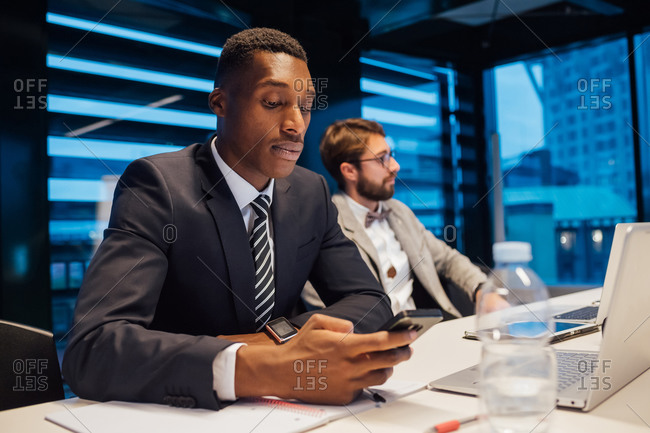 Businessman looking at smartphone during conference table meeting