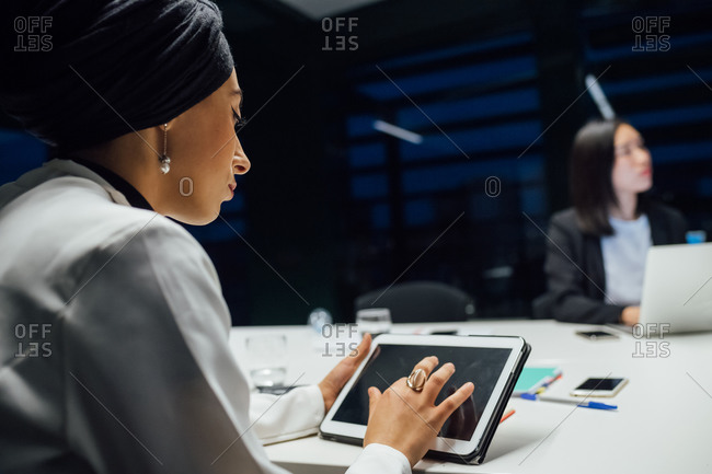 Businesswoman using digital tablet during office presentation, over shoulder view