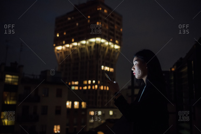 Young businesswoman looking smartphone on office balcony at night