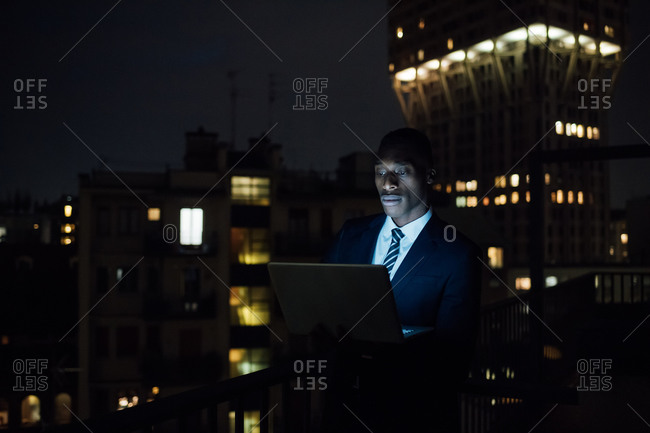 Young businessman using laptop on office balcony at night