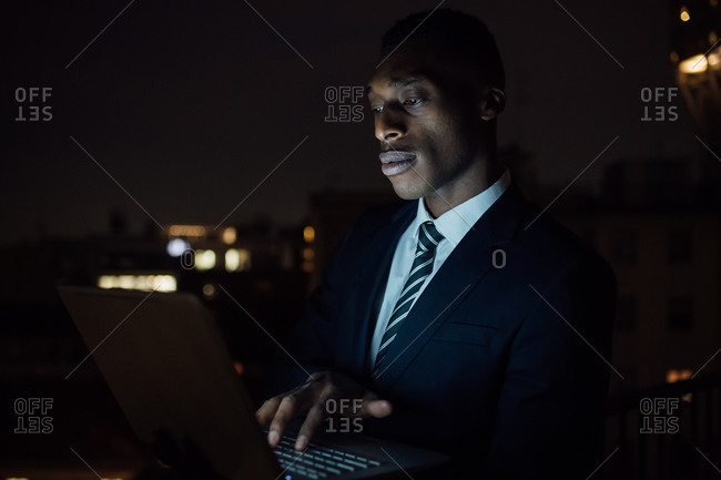 Young businessman typing on laptop on office balcony at night, close up