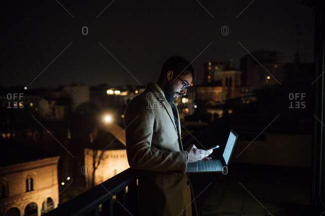 Mid adult businessman looking at smartphone on office balcony at night