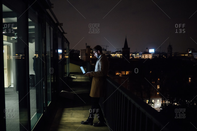 Mid adult businessman looking at laptop on office balcony at night