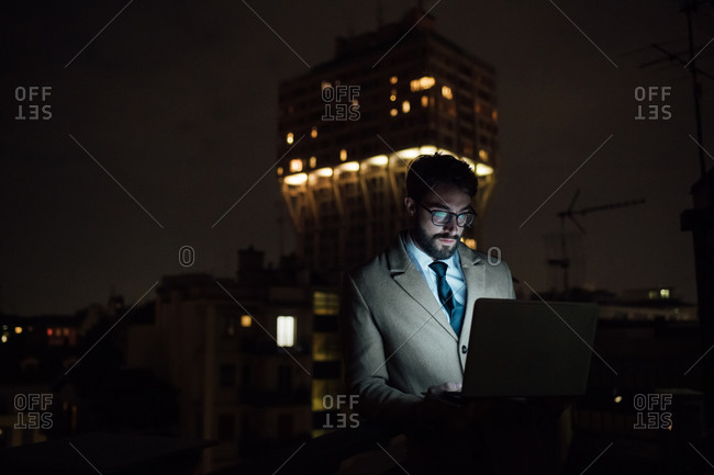 Mid adult businessman typing on laptop on office balcony at night