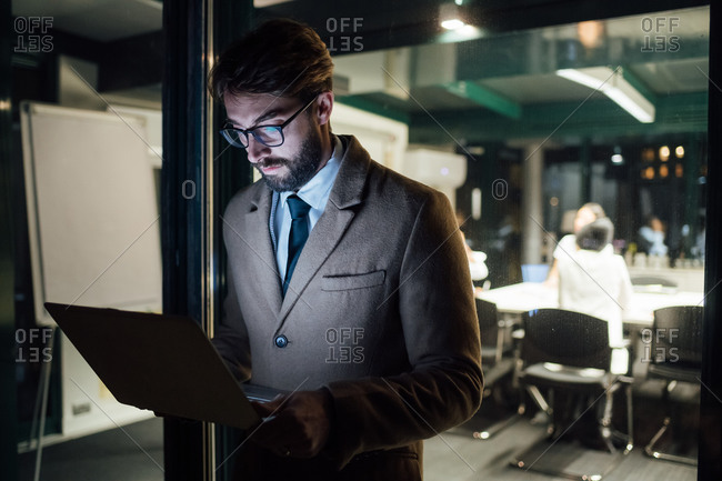 Mid adult businessman looking laptop on office balcony at night