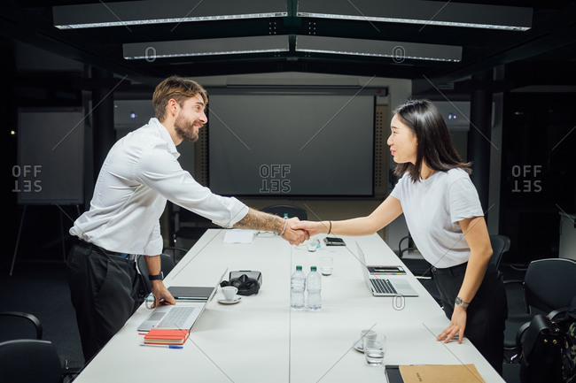 Businesswoman and man shaking hands over conference table