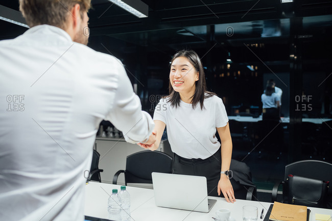 Businessman and woman shaking hands over conference table