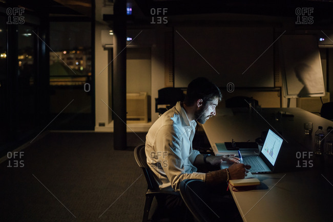 Mid adult businessman in office at night looking at laptop