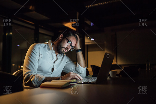 Tired businessman in office at night typing on laptop