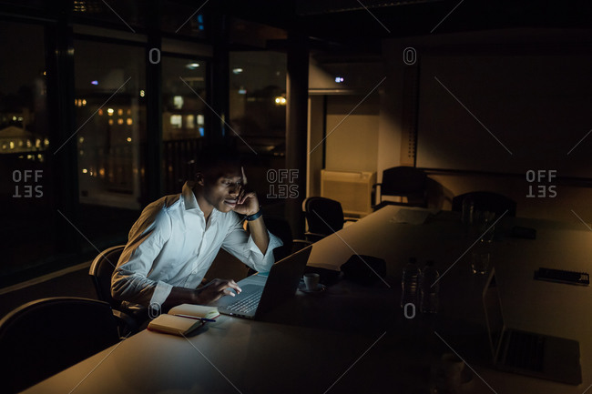 Tired young businessman in office at night typing on laptop