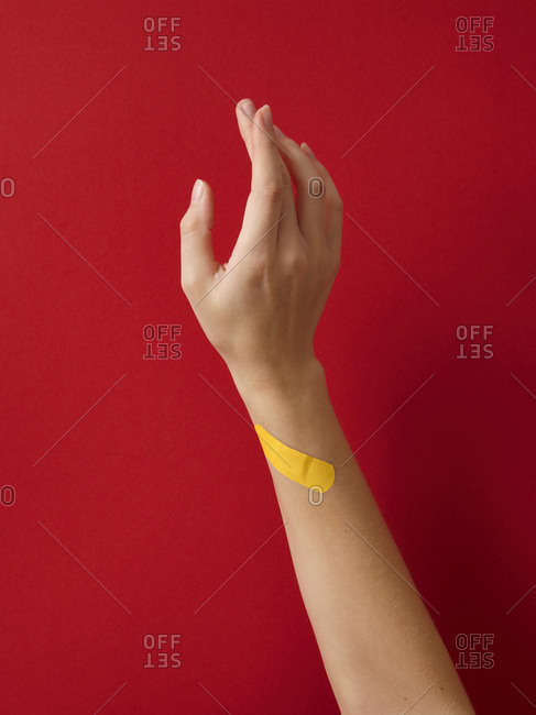 First aid adhesive plaster on woman's wrist against red background