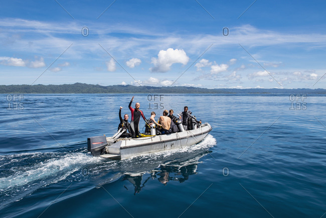 Divers on the way to a dive location, waving from dinghy, Raja Ampat, Sorong, Nusa Tenggara Barat, Indonesia