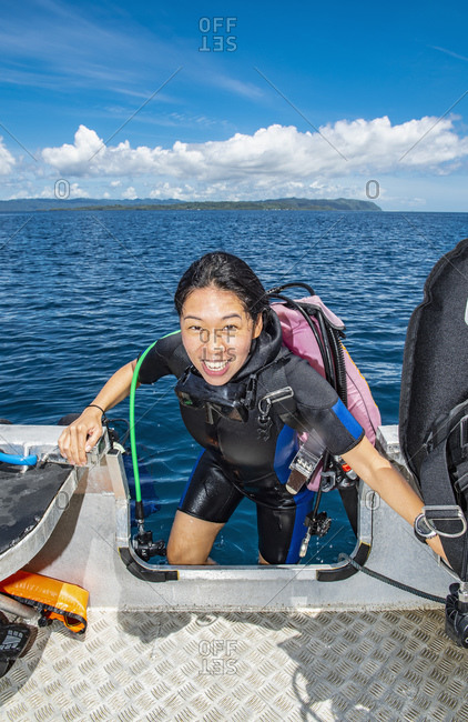 Female scuba diver boarding dinghy after a dive, portrait, Raja Ampat, Sorong, Nusa Tenggara Barat, Indonesia