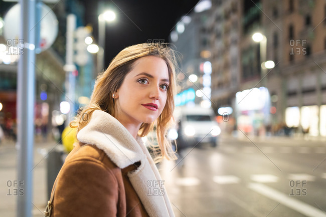 Young woman with long blond hair looking over her shoulder from sidewalk at night, Madrid, Spain