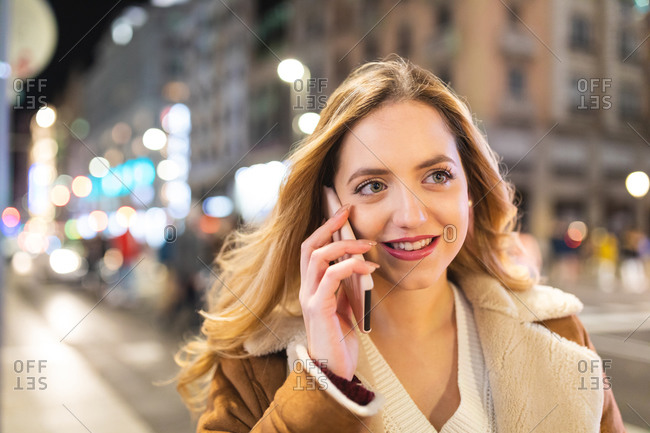 Young woman with long blond hair making smartphone call on sidewalk at night, Madrid, Spain