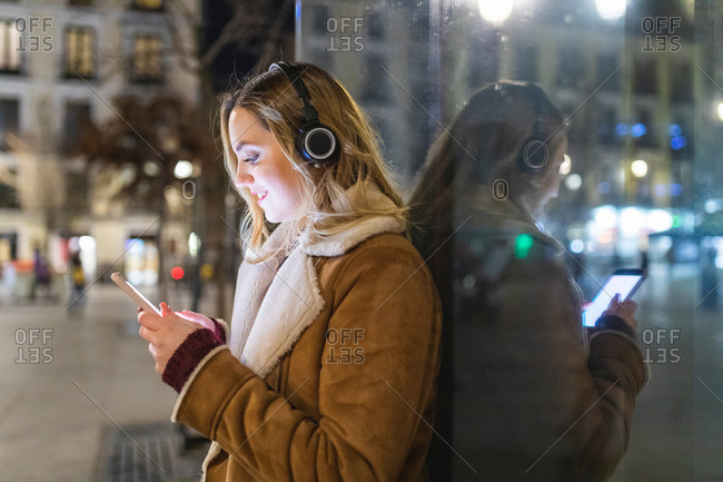 Young woman leaning against shop window listening to headphones and looking at smartphone at night, Madrid, Spain