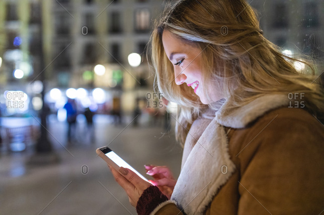 Young woman using smartphone touchscreen on city street at night, Madrid, Spain