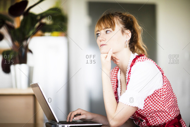 Woman in deep thought, using laptop in home office