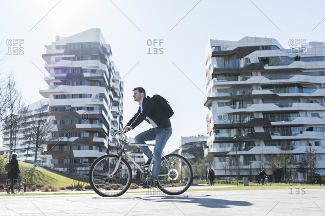 Man cycling past multi-story building, Milan, Lombardia, Italy