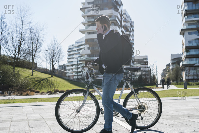 Man pushing bicycle and using smartphone, passing multi-story building, Milan, Lombardia, Italy