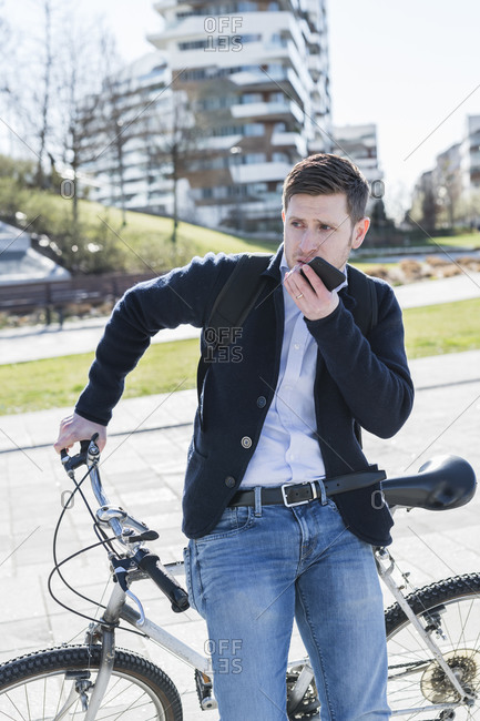 Man talking on smartphone, leaning against bicycle, Milan, Lombardia, Italy