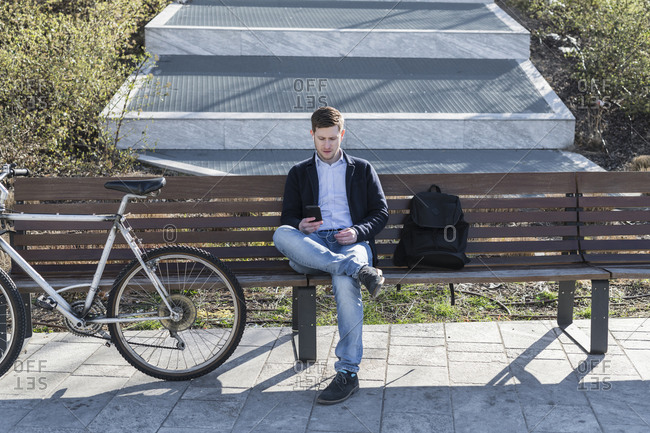 Man using smartphone on park bench, Milan, Lombardia, Italy