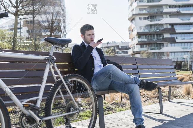 Man talking on smartphone on park bench, Milan, Lombardia, Italy