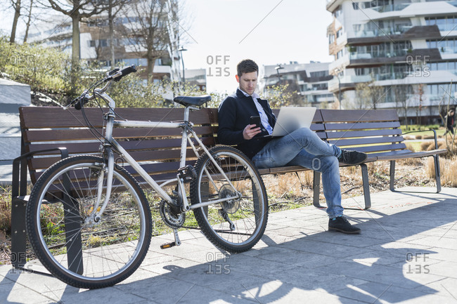 Man using smartphone and laptop on park bench, Milan, Lombardia, Italy