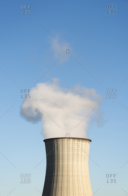 Smoke leaving chimney, cooling tower