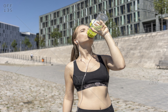 Young woman taking break from exercise and drinking water in city, Berlin, Germany