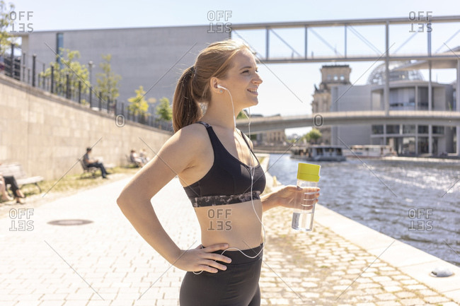 Young woman taking break from exercise in city, Berlin, Germany