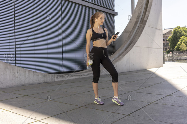 Young woman taking break from exercise and using smartphone in city, Berlin, Germany