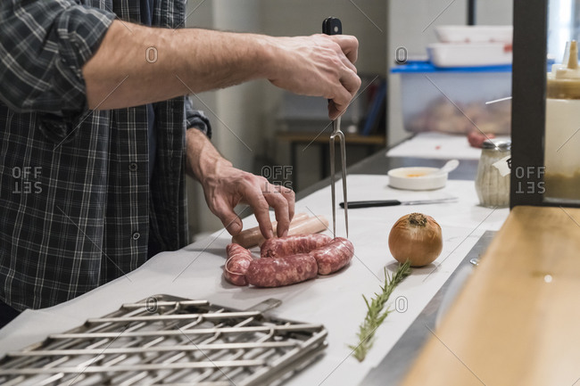 Chef preparing sausages in kitchen