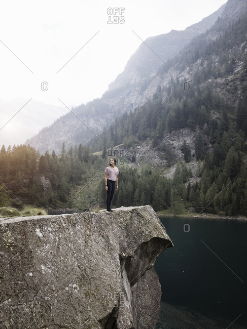 Woman enjoying view by lake, Antronapiana, Piemonte, Italy